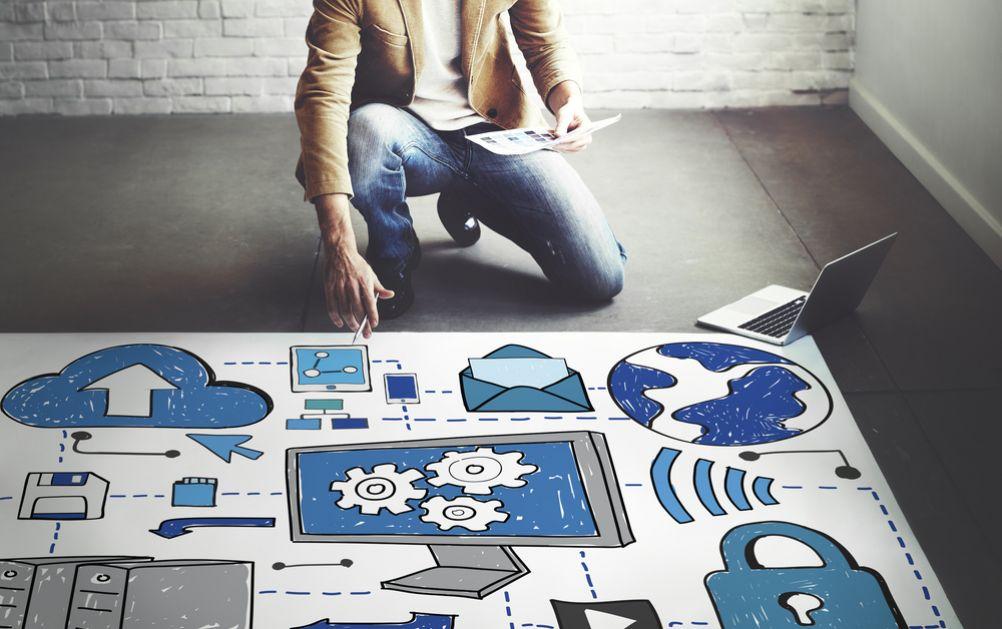 Cloud im Mittelstand: Ein Mann hockt vor einem großen Plan auf dem Boden und denkt nach.