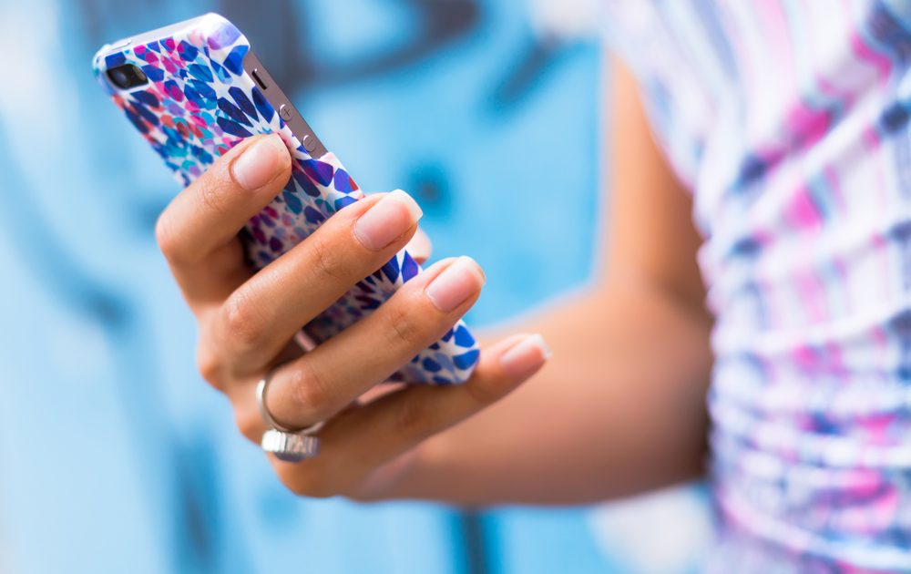 Frauenhand hält Smartphone mit bunter Hülle.