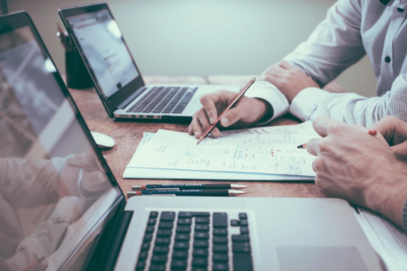 """Titelbild der Studie """"Familienunternehmen im digitalen Wandel"""". Computer stehen auf dem Tisch. Zwei Menschen entwickeln eine Strategie auf dem Papier."""