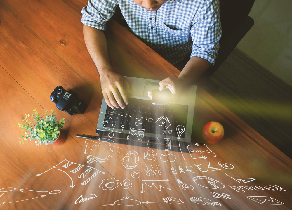 En Mann sitzt an seinem Küchentisch am Laptop und arbeitet virtuell in der Cloud.