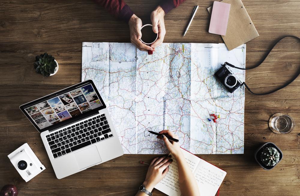 Zwei Menschen sitzen an einem Tisch vor einem Laptop. Vor ihnen liegt eine Landkarte, die den Weg zum Ziel weist.