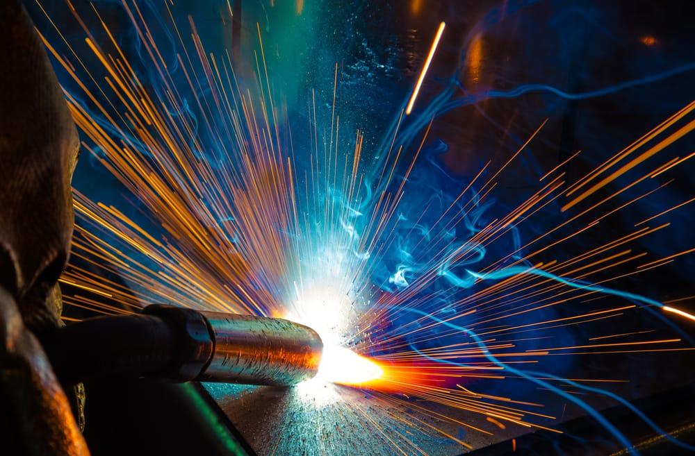 Ein Arbeiter schweißt Metallteile. Funken fliegen durch den Raum.