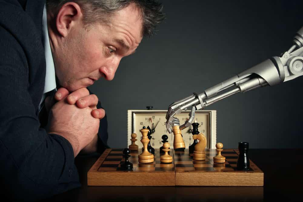 Mann spielt Schach mit einem Roboter.
