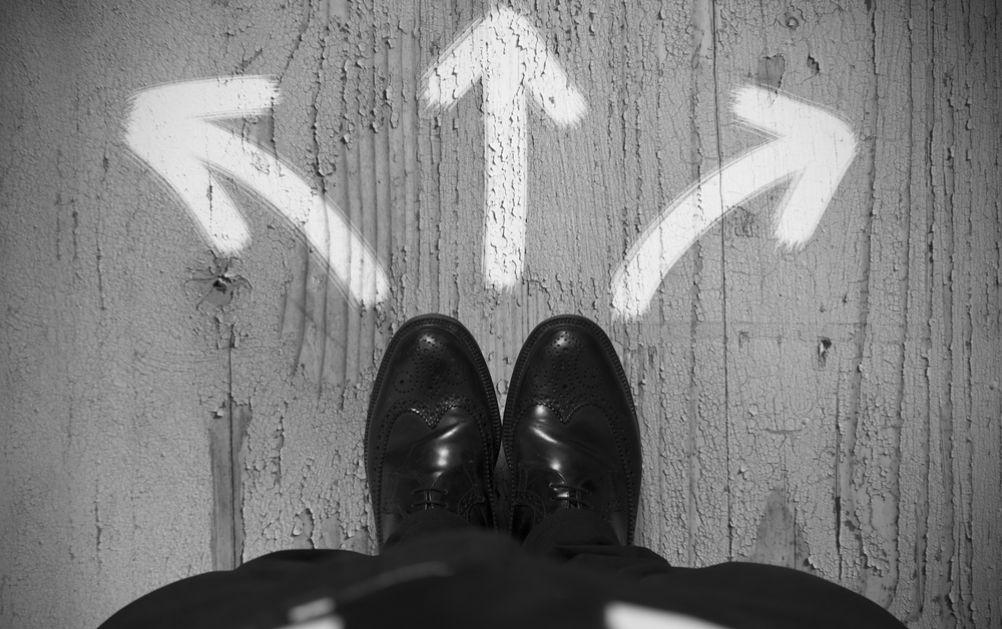 Konzeptbild eines Geschäftsmannes, der in verschiedene Richtungen gehen kann.