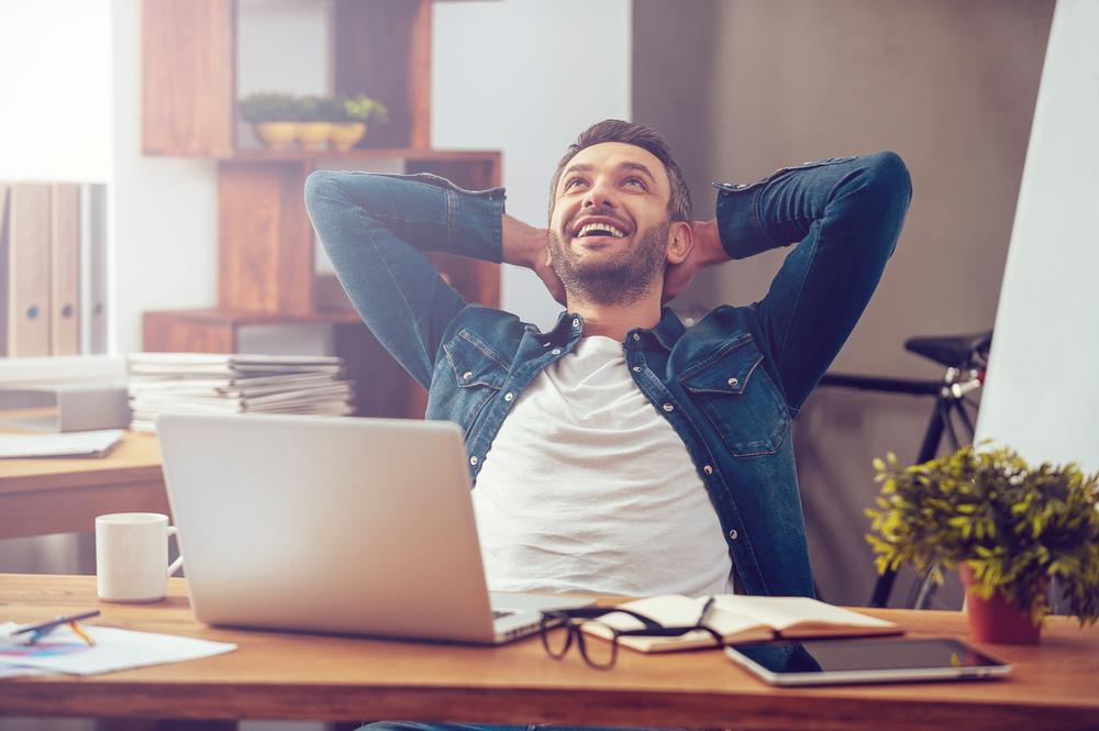 Junger Mann sitzt im Home Office am Laptop, lehnt sich zufrieden lächelnd in seinem Stuhl zurück.