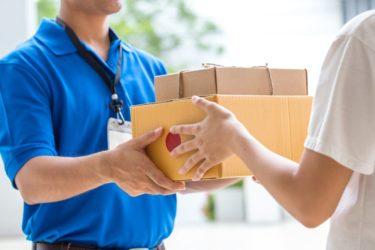 Eine Frau erhält ihre Paketlieferung an der Haustür.