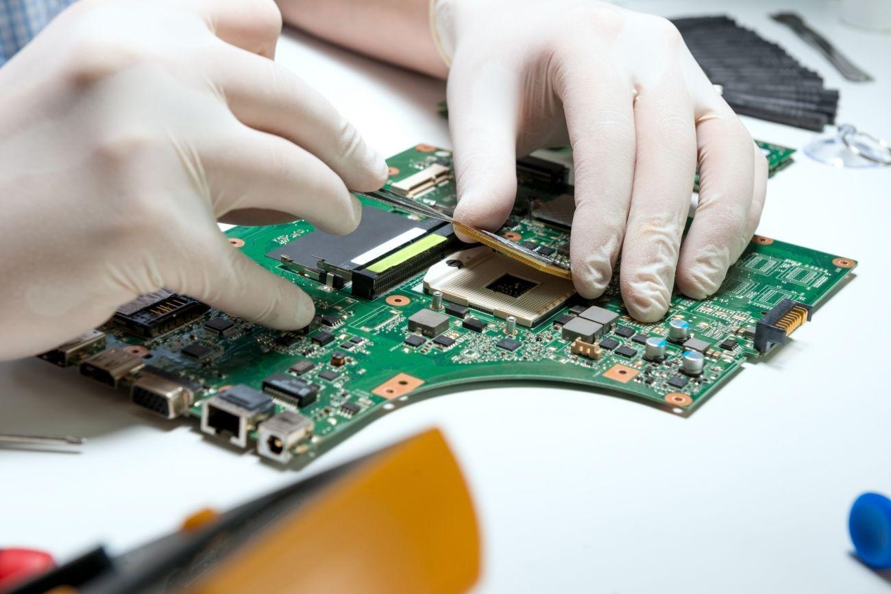 Hände in Handschuhen arbeiten an einer Computerplatine