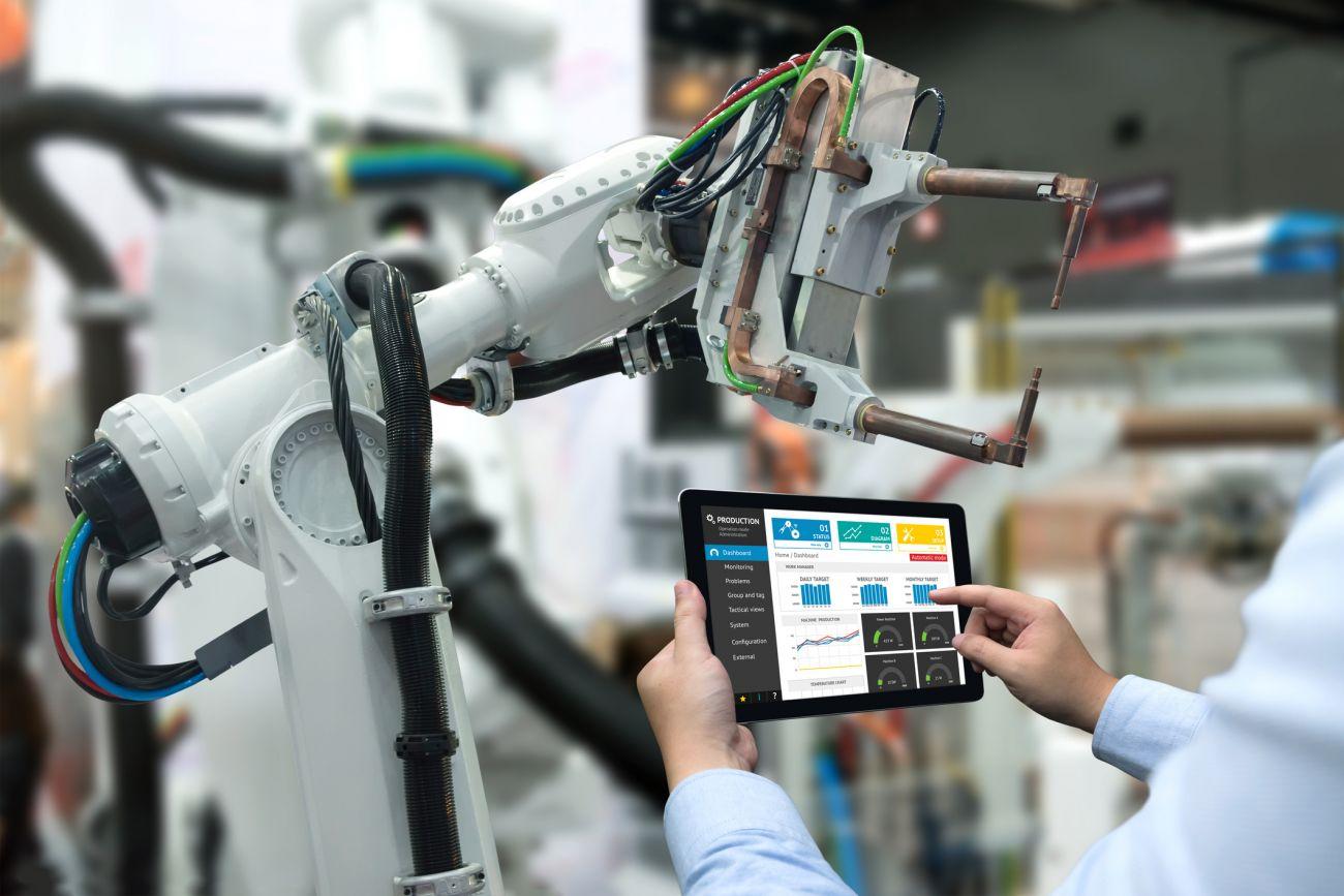 Hand eines Ingenieurs bedient ein Tablet, um in Echtzeit einen schweren Roboterarm zu steuern