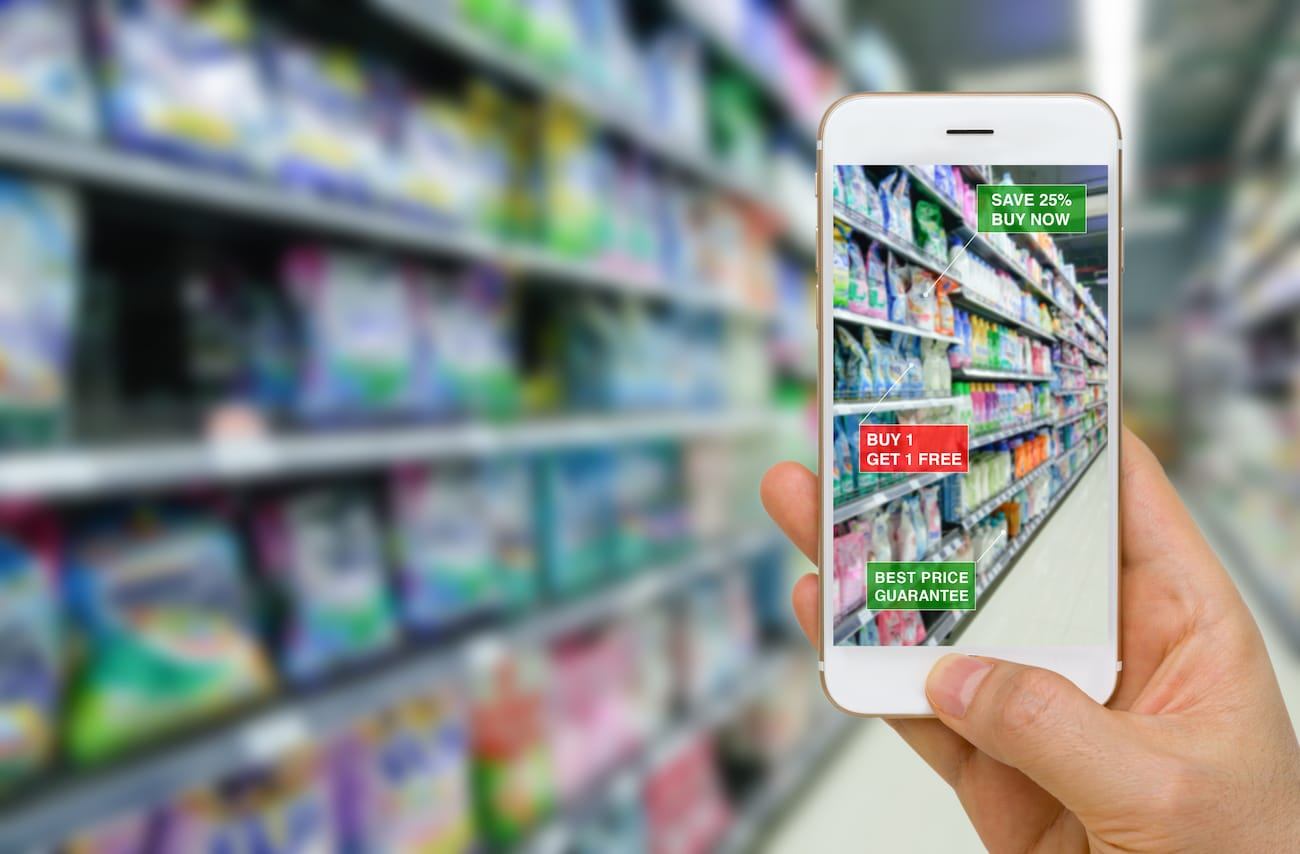 Eine Hand hält ein Smartphone vor ein Warenregal im Supermarkt. Das Display zeigt Informationen zu Angeboten und reduzierten Produkten.