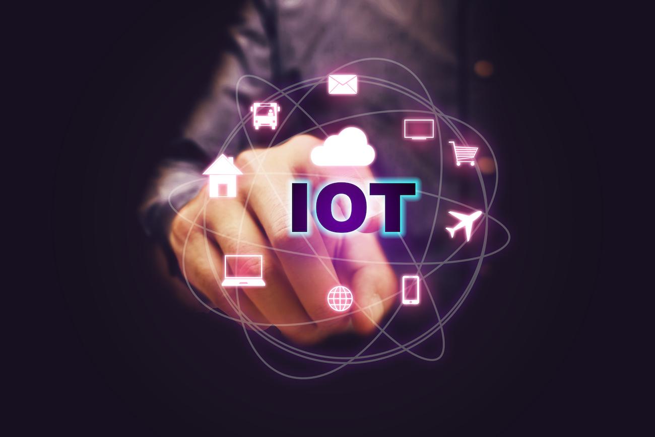 Man zeigt auf IoT-Text mit Internet der Dinge-Symbolen