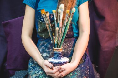 Closeup of female artist hands with paintbrushes