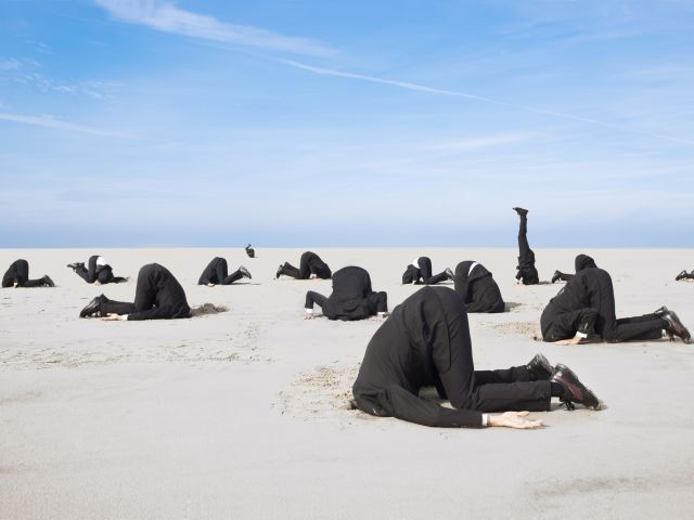 Lots of business man hiding their heads in sand. XXL size image. Bild: © istock.com / Jan-Otto