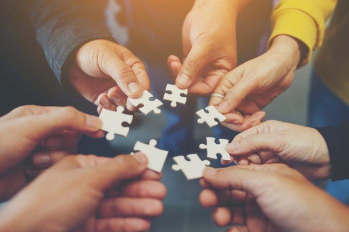 Bild zeigt Hände die Puzzleteile halten
