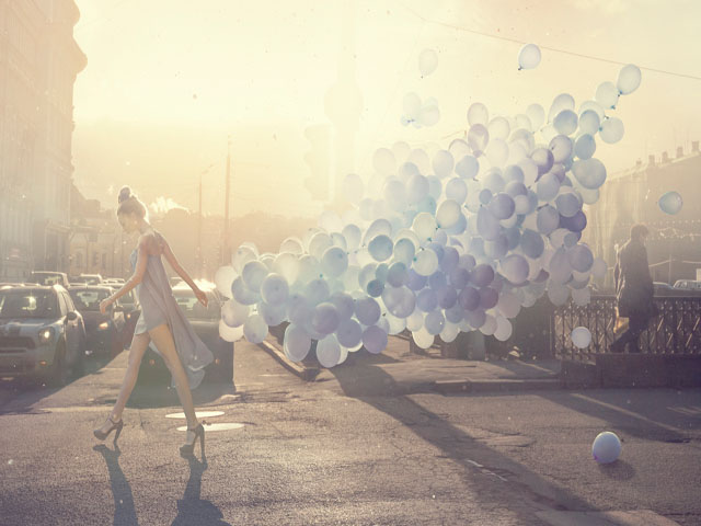 Bild zeigt Dame, die über eine Straße geht und Luftballons hinter sich her zieht. Bild: ©Vizerskaya/ Getty Images
