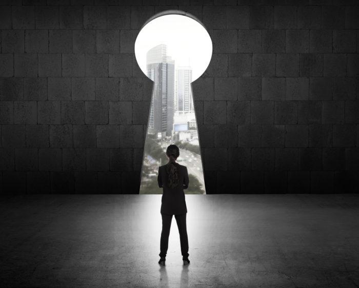 Frau steht vor einem großen Schlüsselloch in der Wand