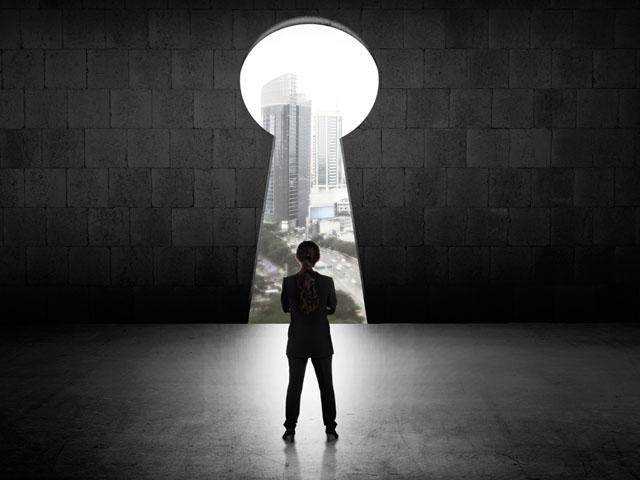 Frau steht vor großem Schlüsseloch in der Wand