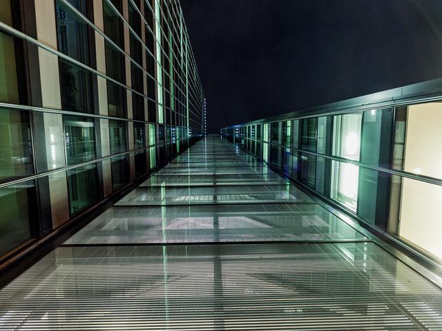 Blick auf ein Glasgebäude von unten in der Nacht