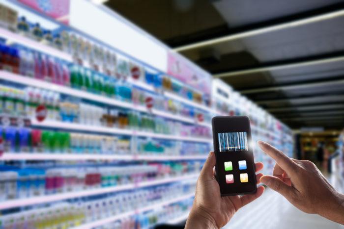 Händer halten ein Smartphone, im Hintergrund ein Supermarktregal. Bild: © Busakorn Pongparnit / Getty Images