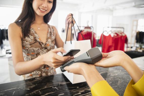 Frau bezahlt an der Kasse mit EC-Karte