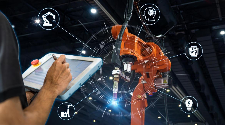 Mann schreibt auf Tablet und programmiert Industrie 4.0-Maschine im Hintergrund