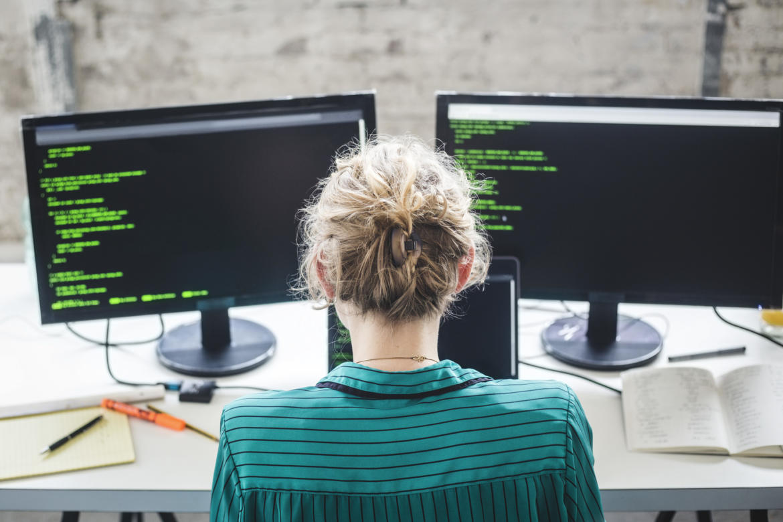 Frau sitzt vor zwei Bildschirmen und programmiert