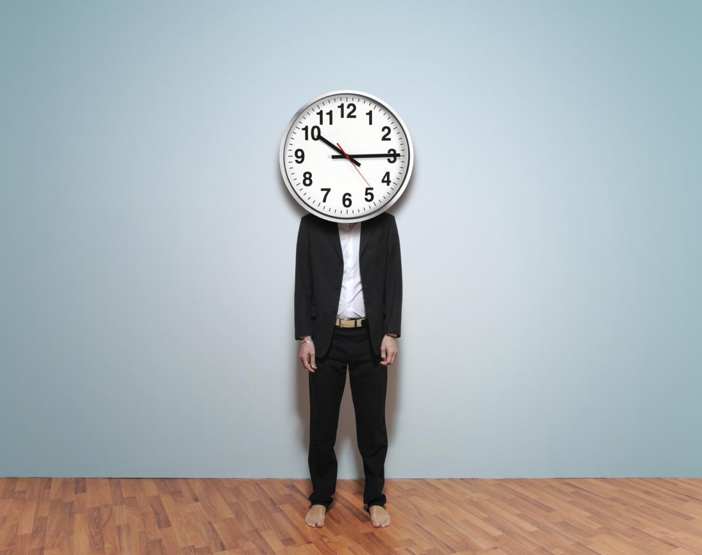 Mann steht vor blauem Hintergrund und trägt Uhr anstatt Kopf