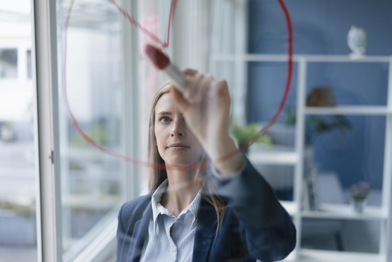 Junge Frau steht im Büro und schreibt mit einem Textmarker auf eine Glasscheibe