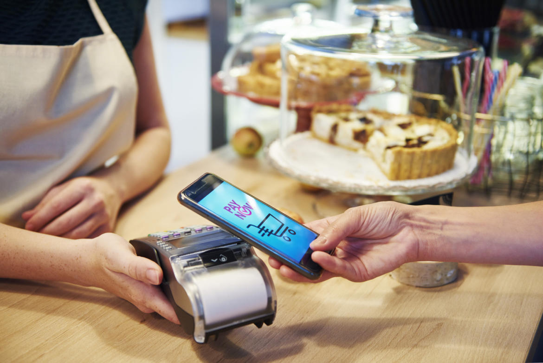 Kundin hält ihr Handy über ein Lesegerät im Café, um zu zahlen