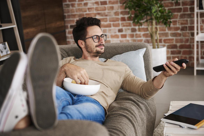 Mann liegt entspannt auf einer Couch und schaut Fernsehen.