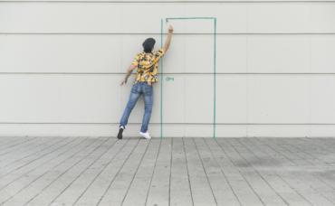 Mann zeichnet mit Kreide eine Tür an eine Mauer.