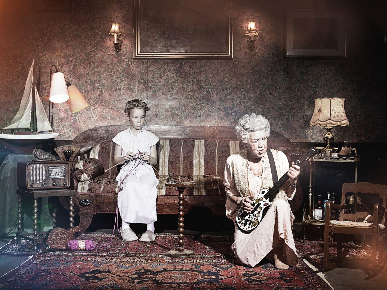 Zwei Frauen im Wohnzimmer, alte Dame mit E-Gitarre