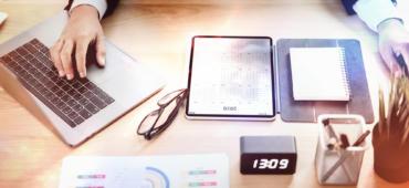 Mann am Schreibtisch, Tablett, Laptop, Brille, Stifte