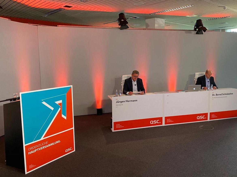 """Jürgen Hermann und Dr. Bernd Schlobohm sitzen in einem Raum neben Schild """"Ordentliche Hauptversammlung"""""""