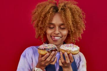 Frau hält zwei Donuts in den Händen und fragt sich, welchen sie essen soll.