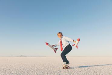 Ein Junge gekleidet als Geschäftsmann fährt Skateboard – anterieben von zwei Raketen, die er in den Händen hält. Bild: © RichVintage / Getty Images