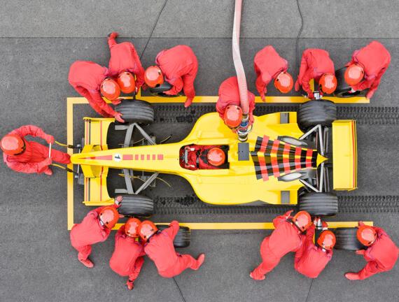 Ingenieure wechseln beim Boxenstopp die Autoreifen und betanken den Rennwagen. Getty Images © David Madison