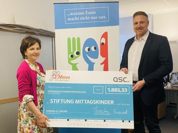 Susann Grünwald von der Stiftung Mittagskinder erhält einen Spendenscheck von Thorsten Raquet, Mitglied der Geschäftsleitung der QSC AG. Bild: © QSC AG.