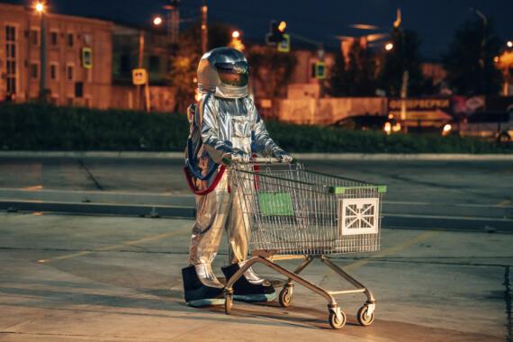 Mensch im Astronautenanzug schiebt Einkaufswagen auf leerem Parkplatz