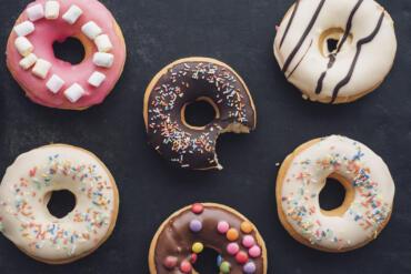 Sechs bunt-verzierte Donuts vor einem schwarzen Hintergrund. Der Donut in der Mitte ist angebissen.