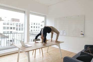 Junge Frau praktiziert Yoga vor ihrem Laptop an ihrem Arbeitsplatz