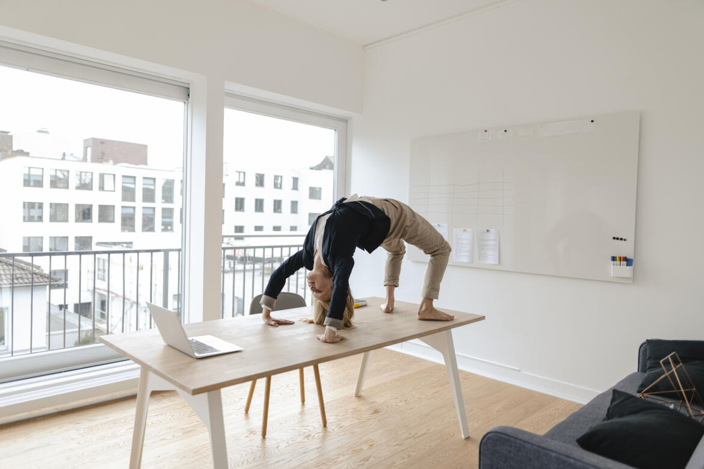 Junge Frau praktiziert Yoga an ihrem Arbeitsplatz