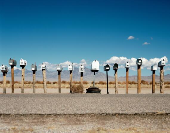 Nebeneinander auf Holzpflöcken aufgereihte Briefkästen vor blauem Himmel und einer Berglandschaft im Hintergrund.