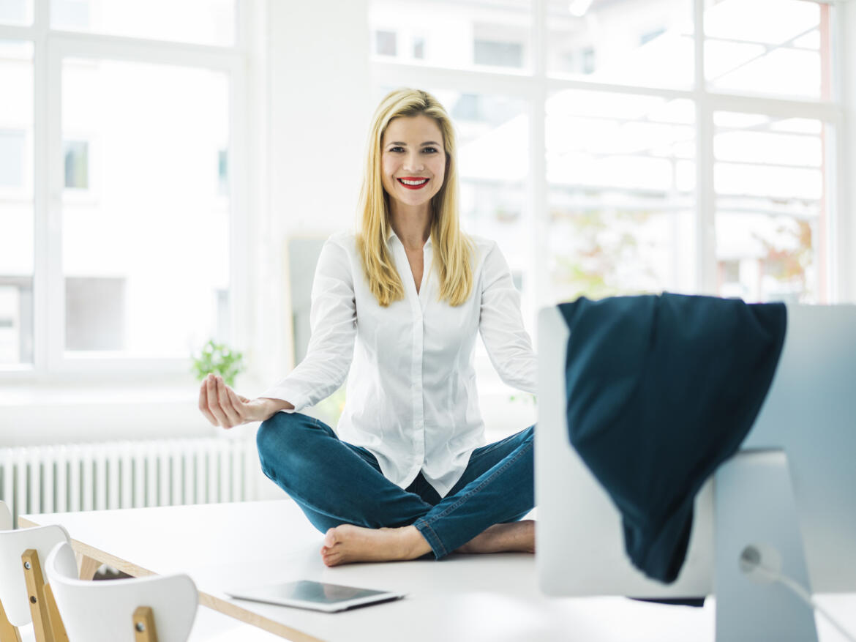 Frau sitzt auf Schreibtisch und macht Yoga
