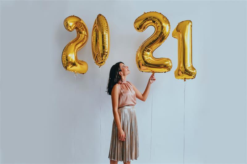 Frau mit goldenen Luftballons auf Silvesterparty feiert das neue Jahr
