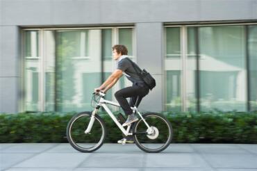 Junger Mann fährt auf E-Bike durch die Stadt