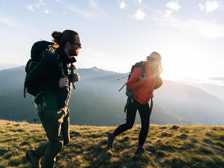 Pärchen beim Bergwandern auf einem Gipfel im Sonnenuntergang